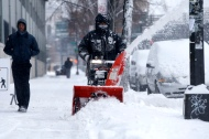 A man clears snow with snow blower in South Bronx section of New York City