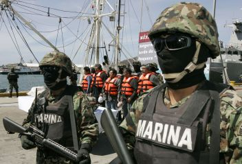 Mexican marines stand guard next to five arrested crew members at a naval base in Salina Cruz in Mexico's state of Oaxaca